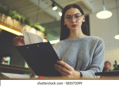 Confident female recruiter of horeca enterprise ready to meet with candidate for vacancy in their restaurant sitting at table reading cv and recommendation from  previous employers searching best one