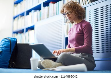 Confident female student using wifi while sitting on the floor at library, she is summarizing information
