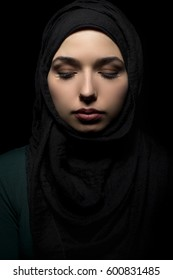 Confident female wearing a black hijab as conservative fashion to represent feminist freedom of expression.  The headscarf is associated with muslims and middle eastern and east european culture.