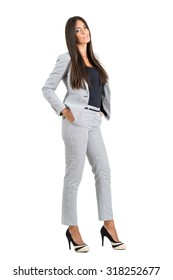 Confident feminine business woman posing with hands in pockets. Full body length portrait isolated over white studio background.