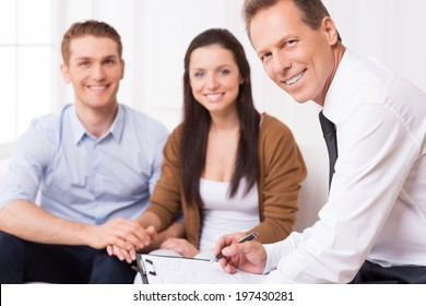 Confident financial expert. Confident mature man in shirt and tie looking at camera and smiling while couple sitting in the background and smiling