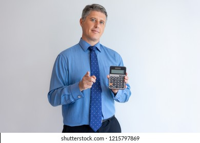 Confident financier advertising loan on favorable terms. Middle aged Caucasian man in formal shirt showing calculator and pointing finger at camera. Profit and accounting concept