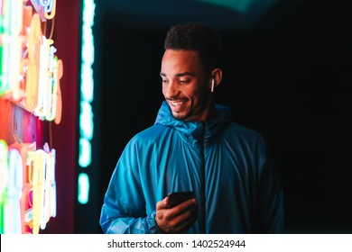 Confident fit young african sports man wearing windbreaker exercising outdoors at night time, using mobile phone