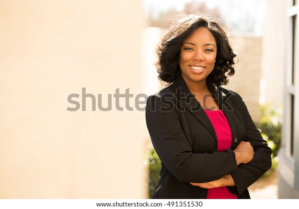 Confident friendly black business woman standing with folded arms.