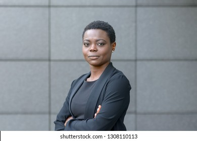 Confident friendly young professional African woman with folded arms and a quiet smile posing side on in front of a grey stone wall with copy space