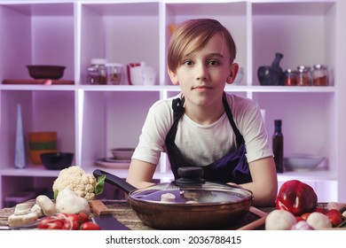 Confident future chef at the kitchen. Boy wearing chef apron. Cooking food concept. Son preparing healthy food for dinner. Boy want to be a professional chef. Table with pan and lot of vegetables.