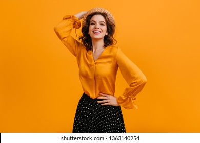 Confident girl laughing at camera. Studio shot of elegant white woman isolated on yellow background.