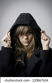 confident girl with misterious look in coat and hand over the hood