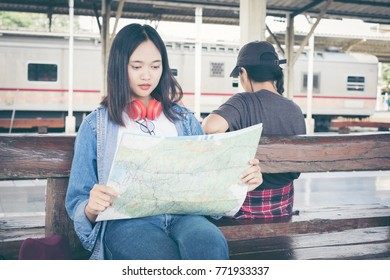 Confident girl traveler examining the map. Young beautiful woman looking map in her hands while sitting on a wooden bench at train station.