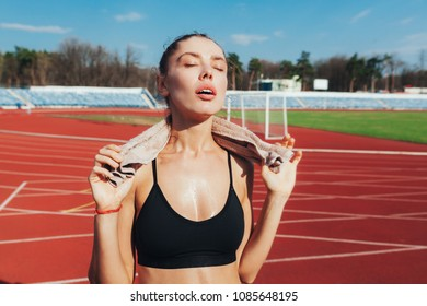 A confident girl woman with a towel around his neck after a hard practice looks ready for more. perspiration workout in the summer