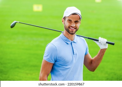 Confident golfer. Young happy golfer carrying driver on shoulder and smiling while standing on golf course