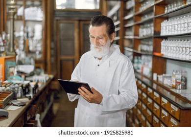 Confident good-looking bearded senior man pharmacist doing inventory in beautiful vintage old pharmacy working with digital tablet