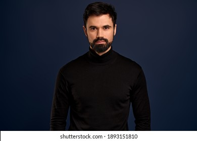 Confident good-looking male entrepreneur in black high neck sweater, smirk and self-assured, standing assertive. Handsome macho man.