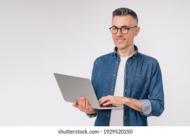 Confident good-looking mature man using laptop isolated over white background
