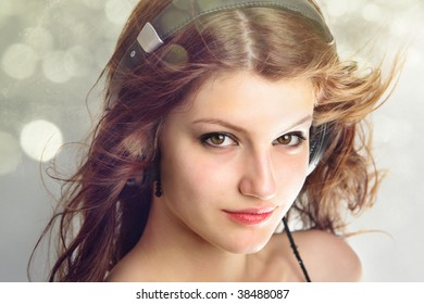 Confident gorgeous teen age girl listening to music showing a lot of pleasure on her face  isolated on bokeh background