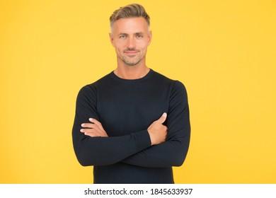 selbstbewusster Typ mit gepflegtem Gesicht. gut aussehender Mann überquerte Hände tragen schwarz. männliche Mode und Schönheit. ein Typ, der stylisch und trendig aussieht. barbershop-Konzept. Kümmern Sie sich um sein Haar.