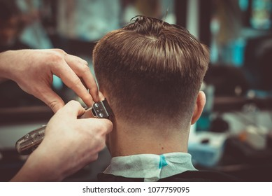 Confident guy sitting at beauty salon . Man haircut. Soft focus.