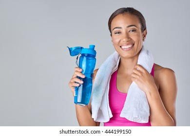 confident gym woman with water bottle smiling isolated in studio