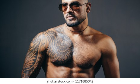 Confident and handsome Brutal man. Man glasses. Stylish sexy man looking away. Handsome brutal man on gray background. Portrait of the brutal handsome male model. Sexy model in aviator sunglasses.