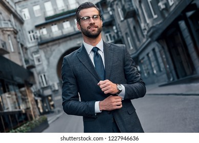Confident and handsome. Full length of young man in full suit smiling while walking outdoors