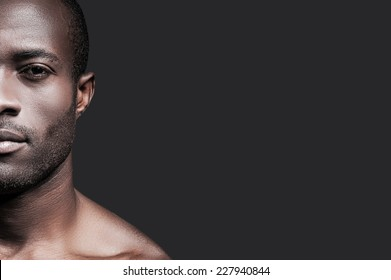 Confident and handsome. Half face of confident young African man looking at camera while standing against grey background