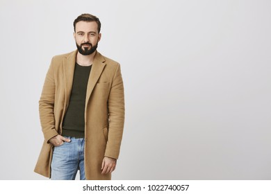 Confident handsome man with a beard and moustache holding his hand in a pocket over white background. Bachelor dressed his best clothes and new coat to impress all girls at the party