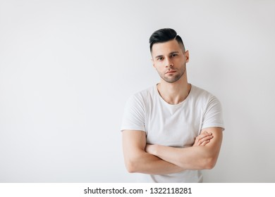 Confident handsome man with crossed arms on white background and copy space