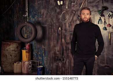 Confident handsome man in the old garage.