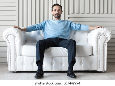 Confident handsome man sitting on a sofa