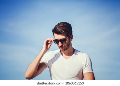 Confident handsome man in sunglasses over blue sky. Men's beauty, fashion.