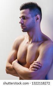 Confident handsome muscular shirtless man with crossed arms