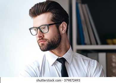 Confident and handsome. Portrait of handsome young businessman in glasses looking away while standing in office