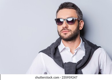 Confident handsome. Portrait of handsome young man in sunglasses and smart casual wear looking away while standing against grey background