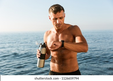 Confident handsome shirtless sportsman holding water bottle while standing at the beach and checking smartwatch