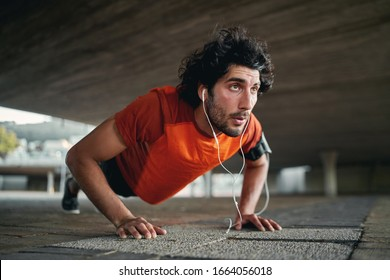 Confident handsome sporty young determined fit man listening music on earphone doing push ups at outdoors