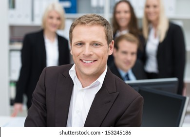 Confident handsome young businessman with a friendly smile seated in the foreground backed by his team, shallow dof