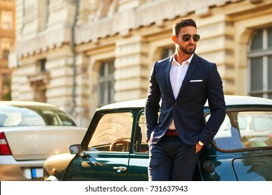 A confident handsome young businessman standing next to his car