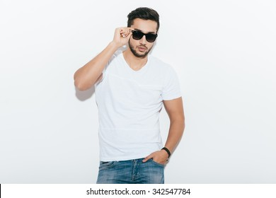 Confident and handsome. Handsome young Indian man adjusting his sunglasses and looking at camera while standing against white background