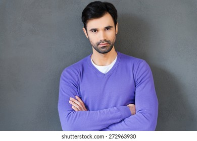 Confident and handsome. Confident young man keeping arms crossed and looking at camera while standing against grey background