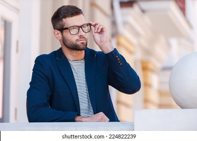 Confident and handsome. Handsome young man in smart casual wear adjusting his eyeglasses and looking away while standing outdoors