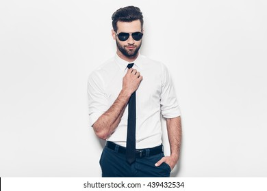 Confident handsome. Handsome young man in white shirt adjusting his necktie and looking at camera while standing against white background