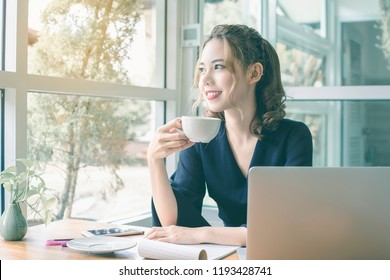 Confident happiness young woman working on laptop or notebook in her office. Beautiful Freelancer Woman working online at her home. Modern life style workin woman.