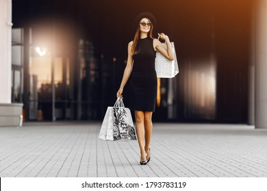 confident, happy, attractive young woman in a black dress and hat, wearing dark glasses, holding shopping bags in front of a shopping center. Black Friday, shopping
