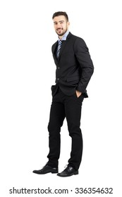Confident happy business man with hands in pocket side view.  Full body length portrait isolated over white studio background.