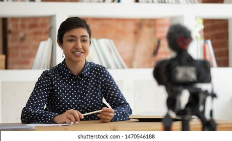 Confident happy indian millennial girl sitting in front of camera, recording self-introduction or educational video for online university course. Smiling business woman sharing professional knowledge.