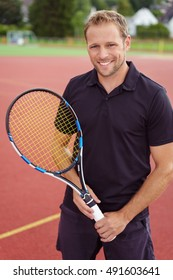 Confident happy male tennis player standing on an outdoor all weather court with his racket in his hands smiling at the camera