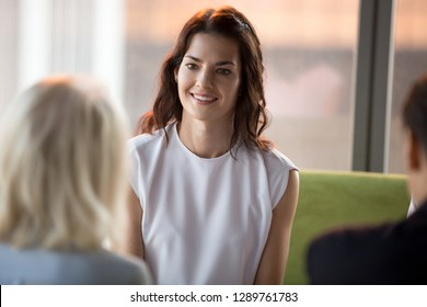 Confident happy millennial seeker applicant smiling looking at hr during job interview, young smiling businesswoman participating business meeting negotiations, recruiting, first impression concept