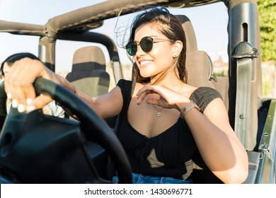 Confident happy woman driving SUV during summer trip