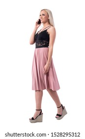 Confident happy young blonde woman in elegant clothes walking and talking on the phone looking up. Full body isolated on white background.