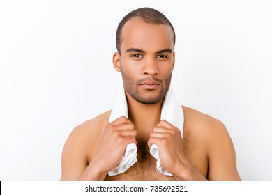 Confident harsh young mulatto nude man is standing on the pure white background, with towel around his neck. So hot and attractive, fashionable and brutal, smooth nice clean skin, light stubble
